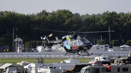 A helicopter lifts off at Pocono Raceway carrying