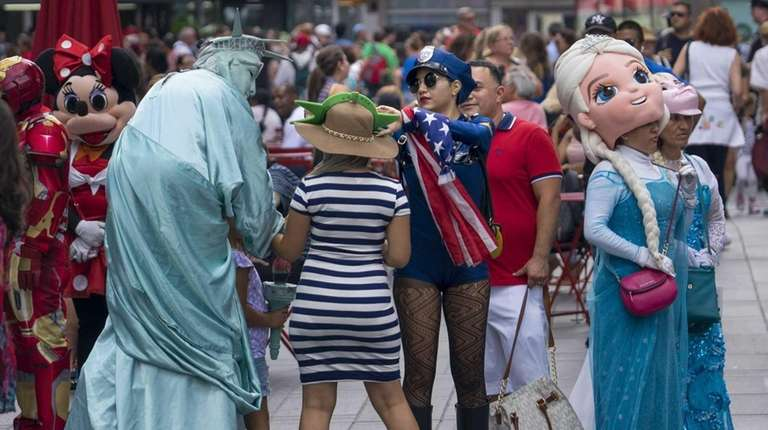 Characters now common to Times Square mingle with