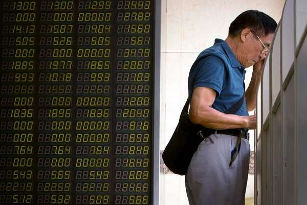 A Chinese investor monitors stock prices on a