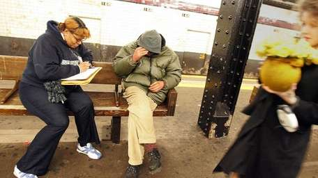 Volunteer Vanessa Thompson (L) interviews a homeless
