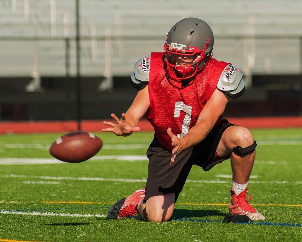 Connetquot's Jack Cassidy takes the snap during practice