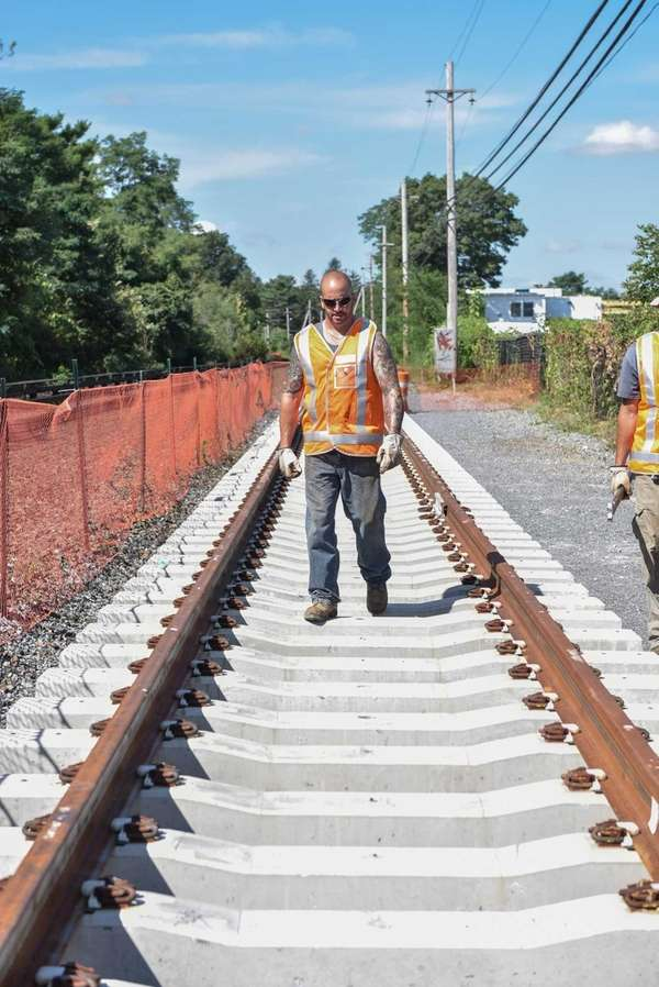 A LIRR worker walks along the first section
