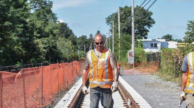 A LIRR worker walks along the first section