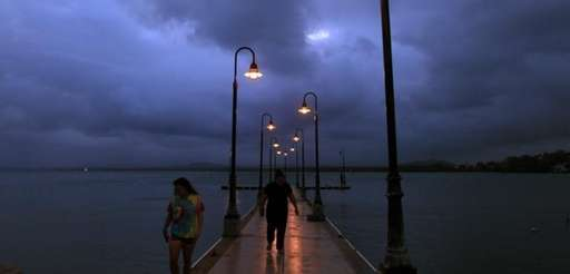 A couple walks on a pier under cloudy