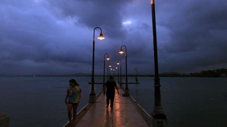 A couple walks on a pier under cloudy