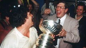Islanders head coach Al Arbour, right, celebrates winning