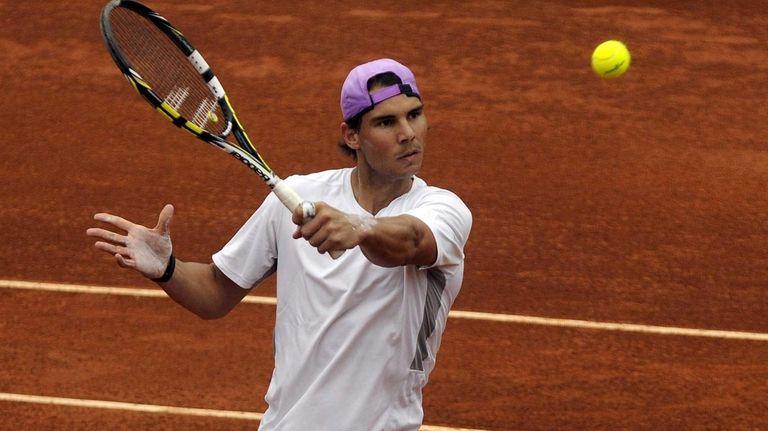 Rafael Nadal returns a ball during a training