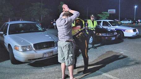A motorist is searched at an overnight sobriety
