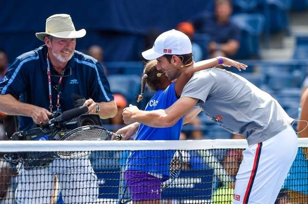 Novak Djokovic hugs a participant during Arthur Ashe