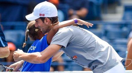 Novak Djokovic hugs a participant during Arthur Ashe