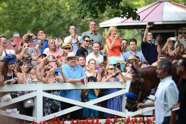 Spectators gather to view American Pharoah, right, in