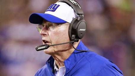 Giants head coach Tom Coughlin stands on the