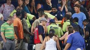 Rescue workers carry an injured fan from the