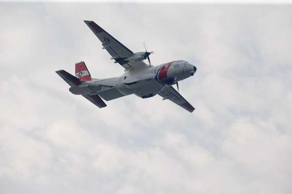 A Coast Guard aircraft flies over the area