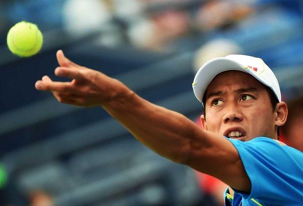 Japan's Kei Nishikori serves to France's Benoit Paire