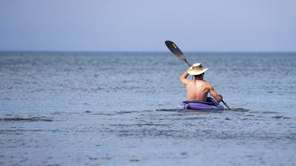 A man kayaks along the Long Island Sound
