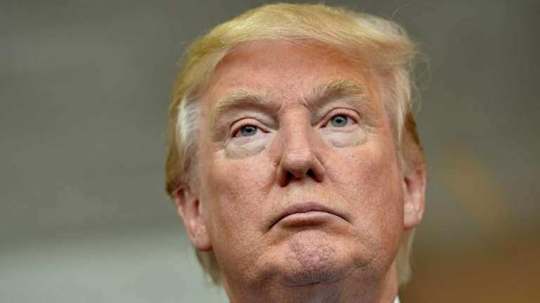 Donald Trump listens during a news conference in