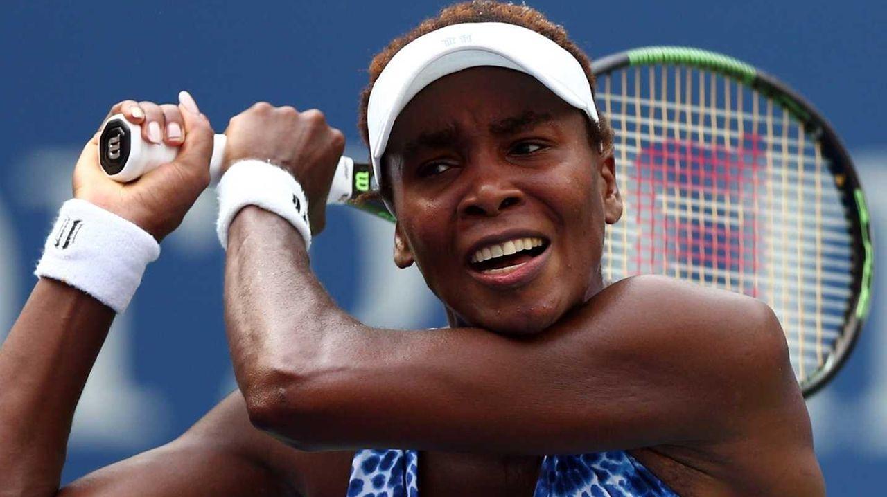 Venus Williams returns a shot against Monica Puig