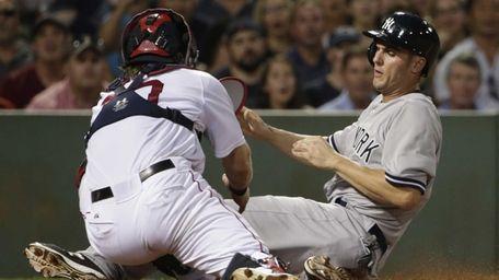 The New York Yankees' Greg Bird, right, slides