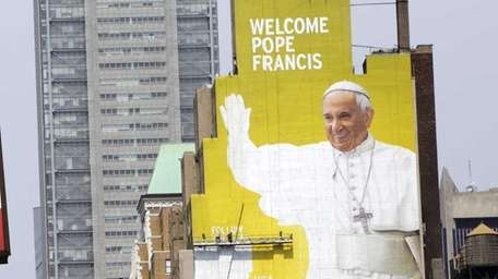 Sign painters work on a portrait of Pope