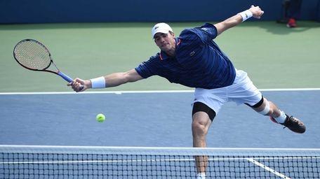 John Isner comes to the net against Malek