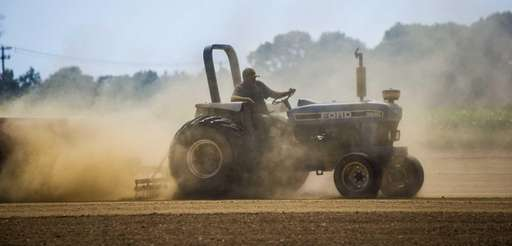 A tractor travels along a farm field in