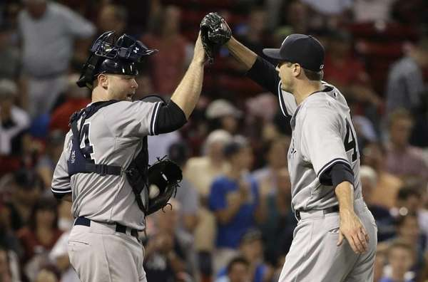 New York Yankees catcher Brian McCann, left, celebrates