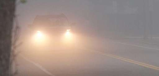 A car drives through the fog in Westhampton