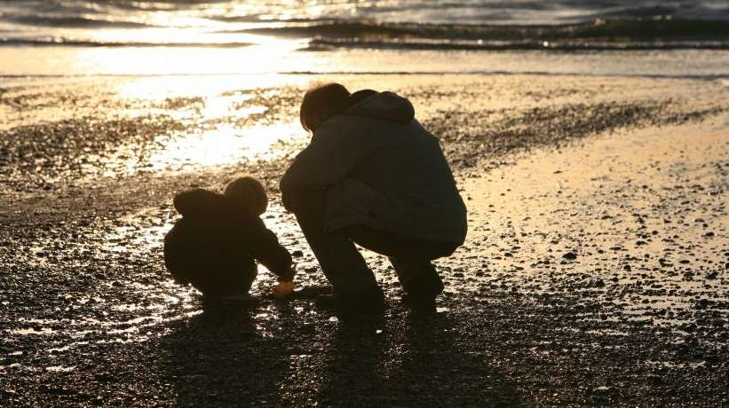 A parent and child at the beach.