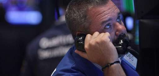 A trader watches his screens warily Tuesday, Sept.