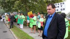 Christian Killoran right, stands with protesters who support