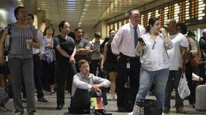 Commuters at Penn Station wait for train service