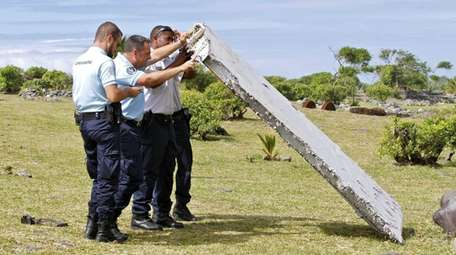 French police officers inspect debris, now confirmed to