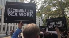 Demonstrators hold signs Thursday, Sept. 3, 2015, as