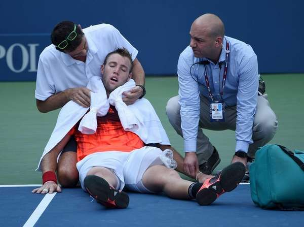 Jack Sock is assisted after he collapses on