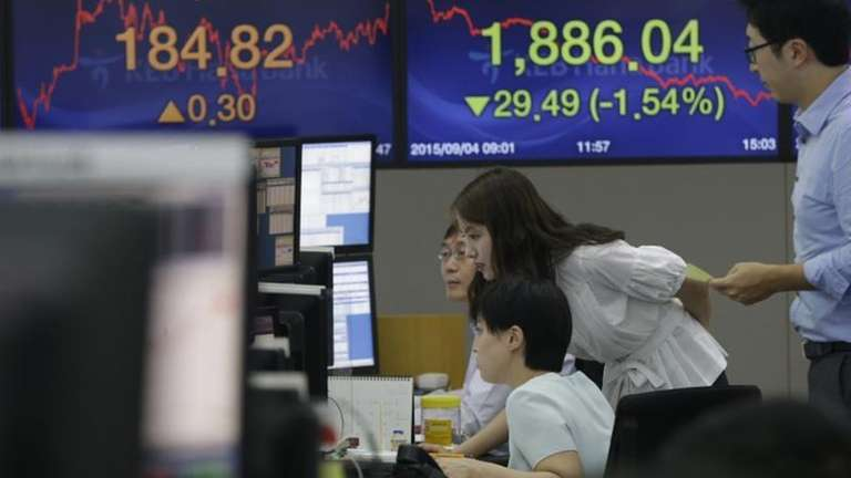 Currency traders watch monitors at the foreign exchange