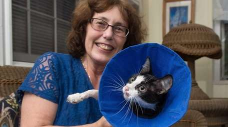 Suzanne Coopersmith holds Lie-la, the cat she helped