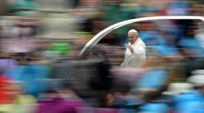 Pope Francis greets the crowd from the popemobile
