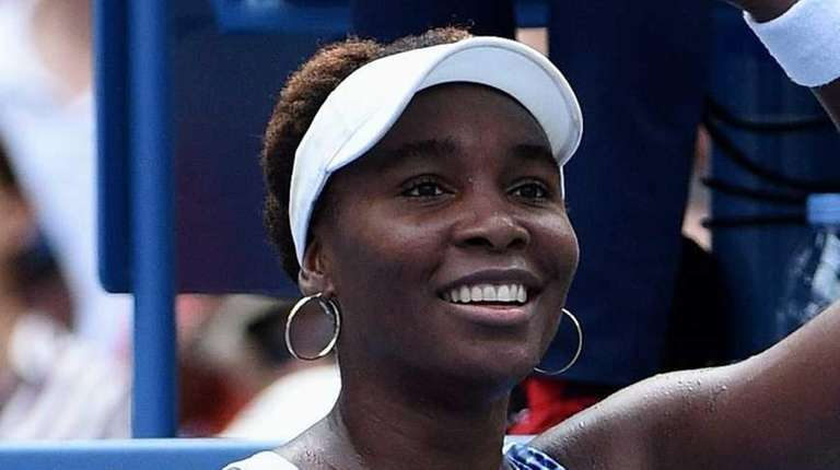 Venus Williams waves to fans after she wins