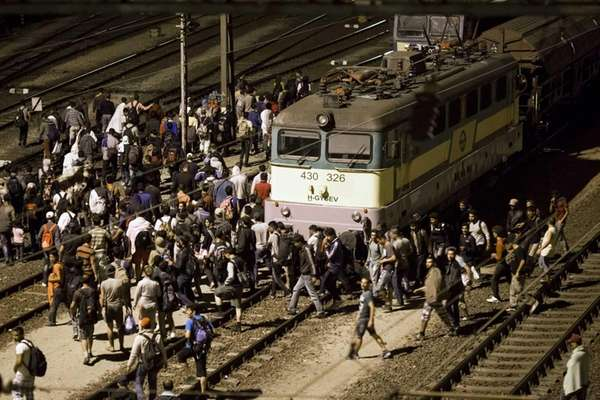 Refugees walk on the tracks at the Tatabanya