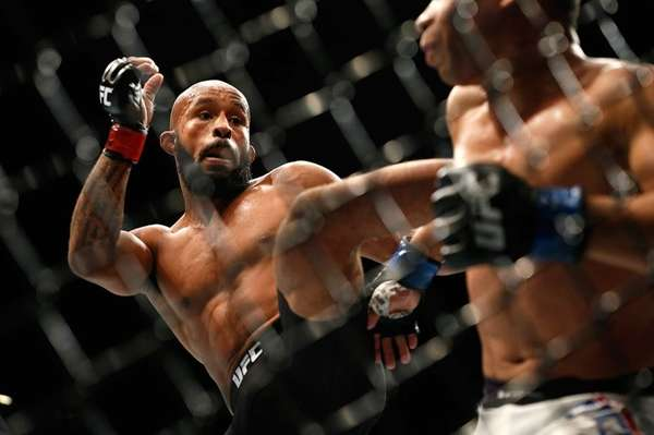 Demetrious Johnson kicks John Dodson during their flyweight