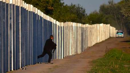 A migrant runs after he enters the territory