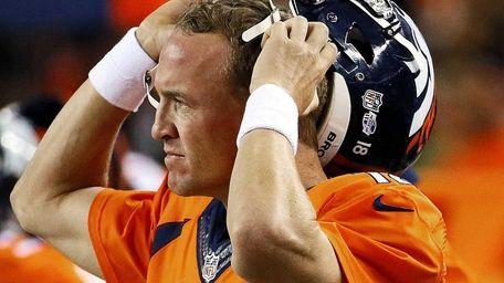 Denver Broncos quarterback Peyton Manning (18) watches from