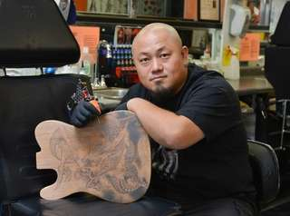 Tattoo artist Zhang Po holds a wooden guitar
