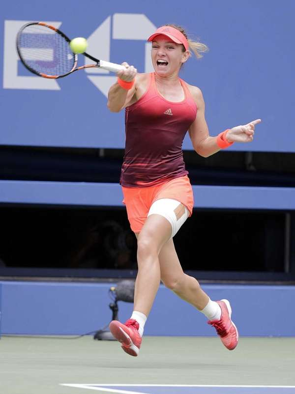 Simona Halep hits a running forehand return to