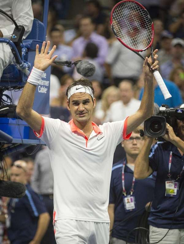Roger Federer waves to the fans after defeating