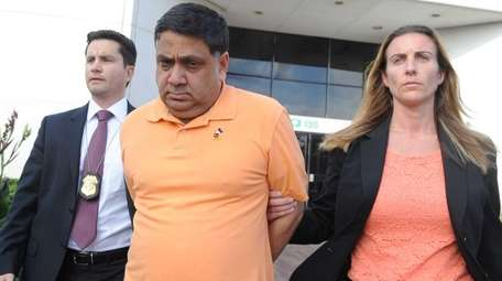 Harendra Singh is led out of the FBI