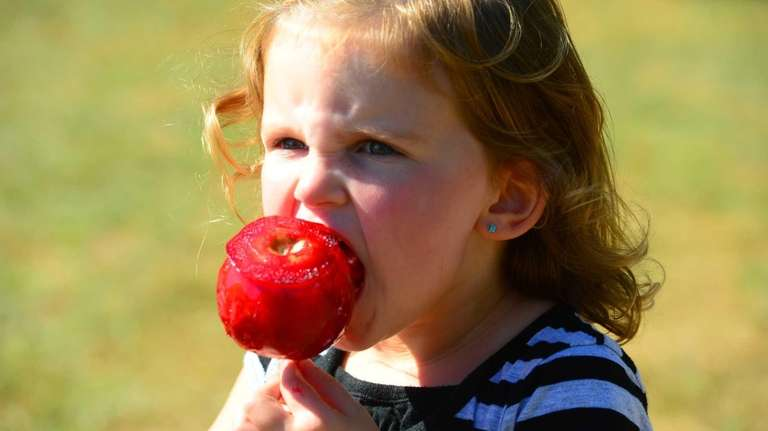 Two-year-old Anna Worontzoff enjoys a candy apple at