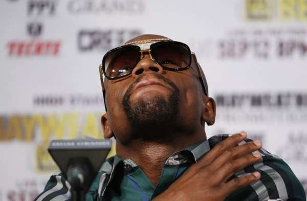 Boxer Floyd Mayweather Jr. watches during a news