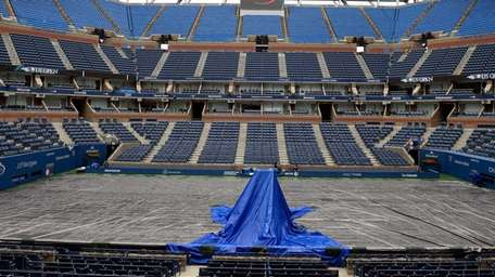A tarp covers the court on Arthur Ashe
